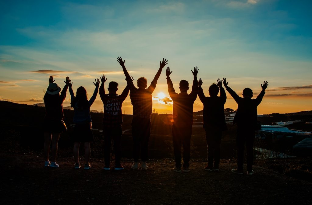 Image of multiple friends with their hands to the sky