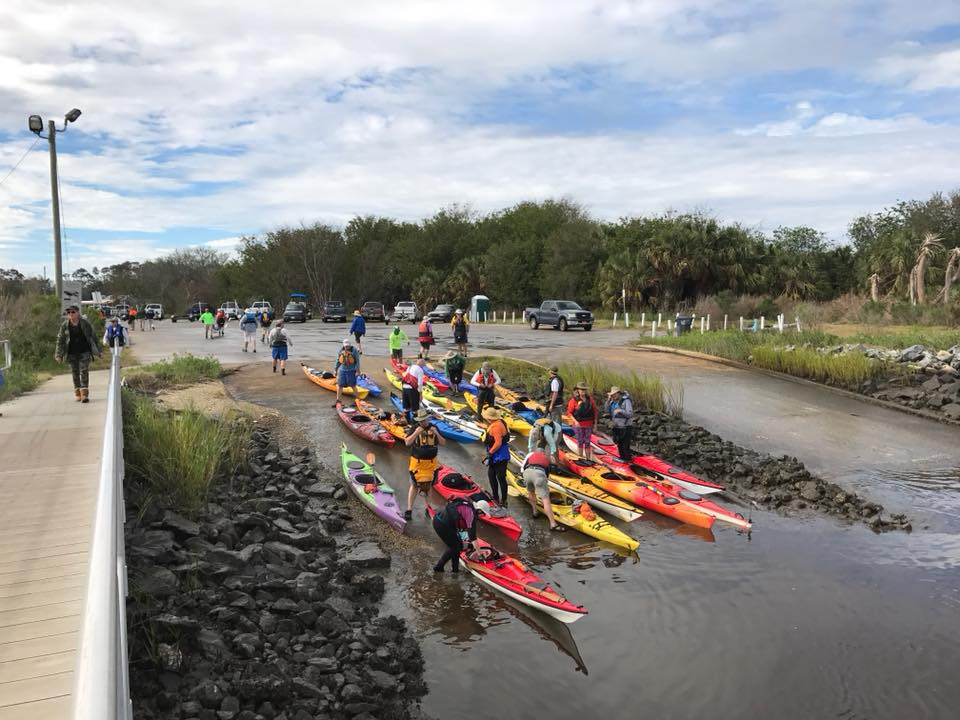 Picture showing multiple people getting ready to Kayak